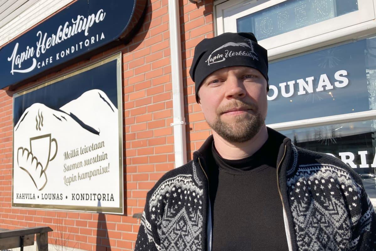 Konditoria-kahvilayrittäjä Matti Hiltunen tummassa neuletakissa. Taustalla tiiliseinää, jossa Hiltusen yrityksen Lapin herkkutuvan mainoskyltti.