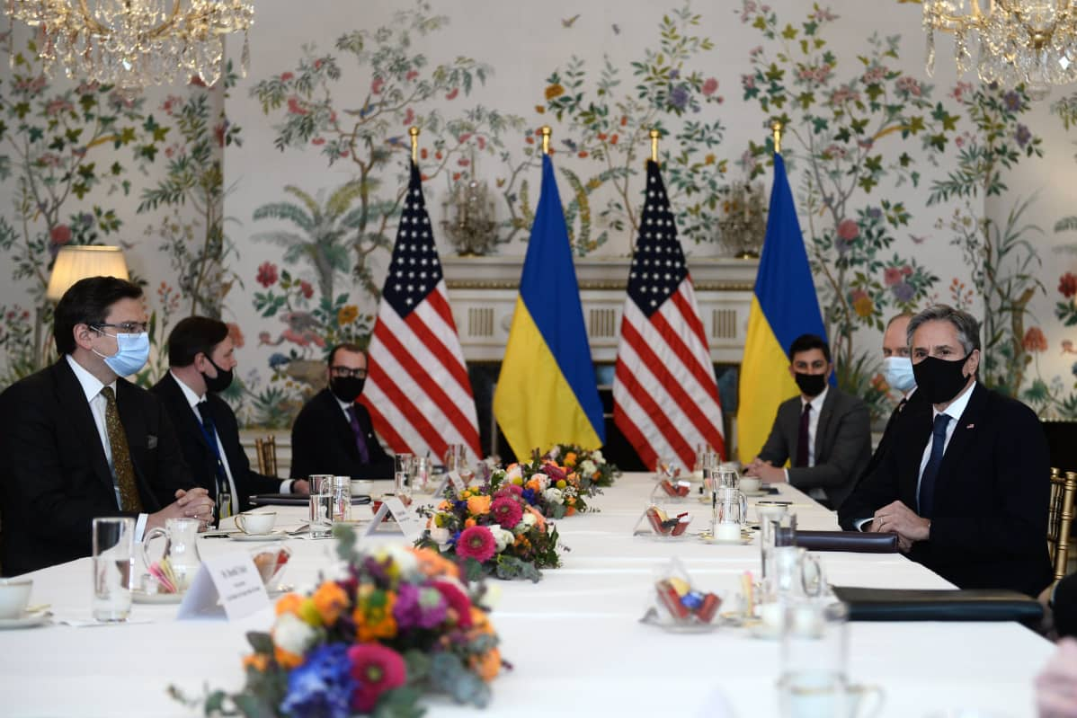 Mnisterit ja muut virkamiehet istuvat pitkän valkoisella pöytäliinalla peitetyn pöydän vasremmalla ja oikealla puolella. Miehillä on tummat puvut ja maskit. Seinän vieressä on molempien maiden liput.