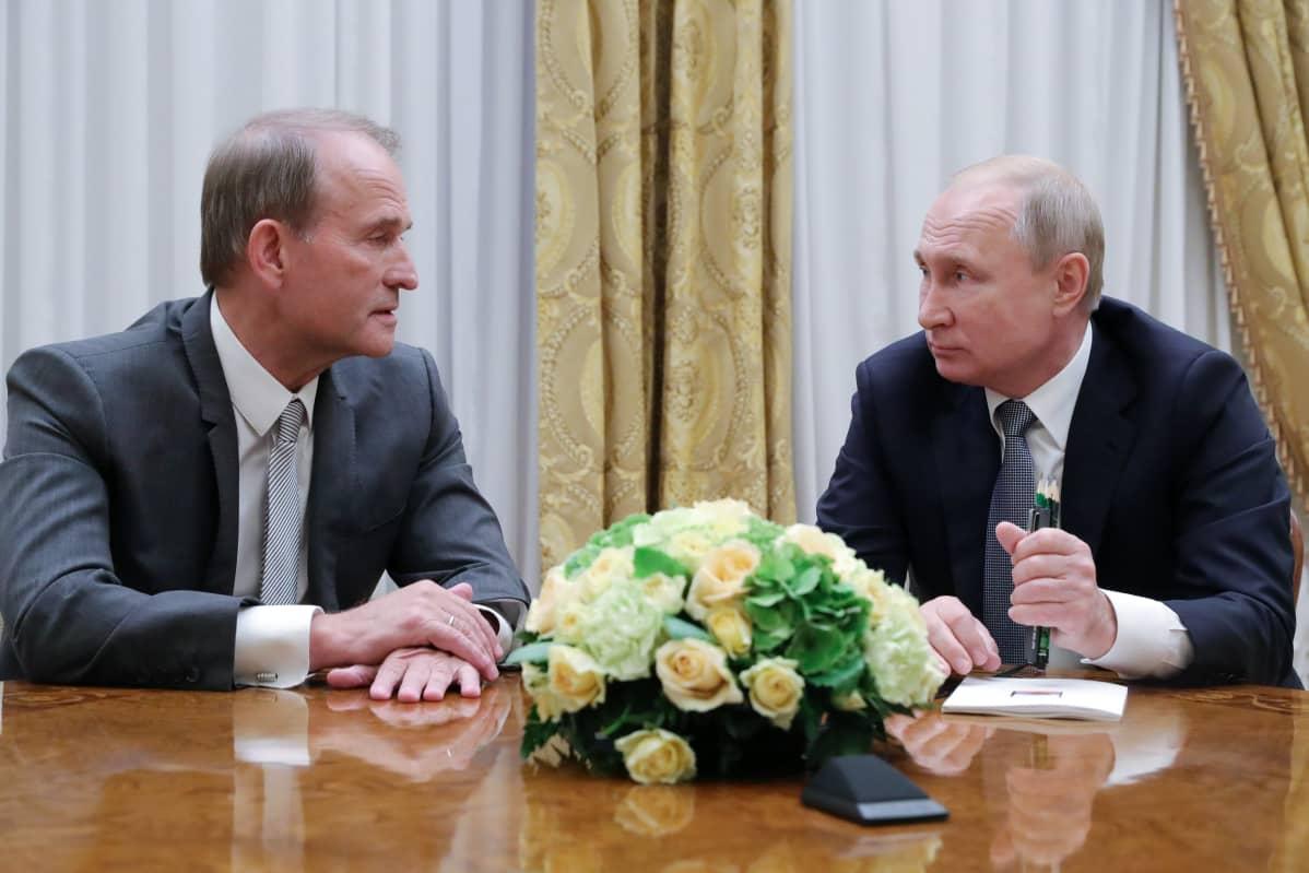 Medvedtshuk ja Putin istuvat pöydän ääressä. Medvedtshuk puhuu ja Putin kuuntelee. Medvedtshuikilla on tummanharmaa puku, Putnilla tumma. Päydällä heidän keskellään on kukka-asetelma.