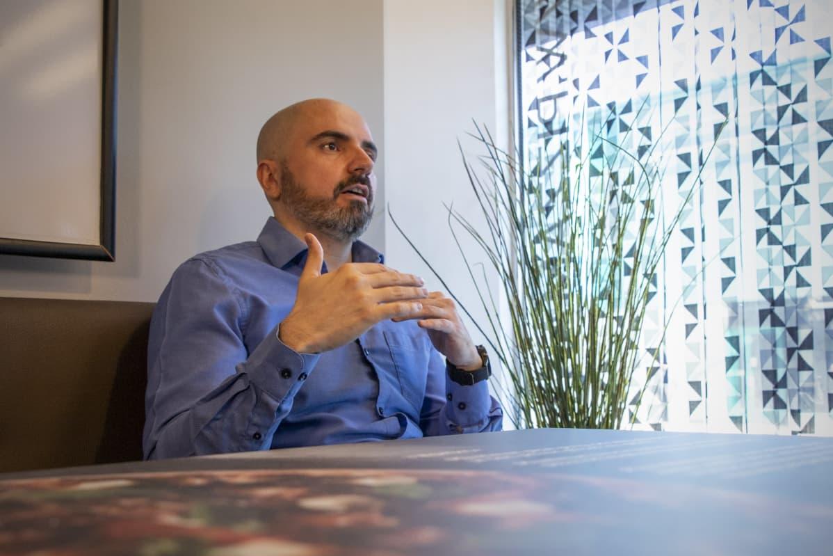 Ali Giray istuu pizzeriassaan tyhjän pöydän ääressä.