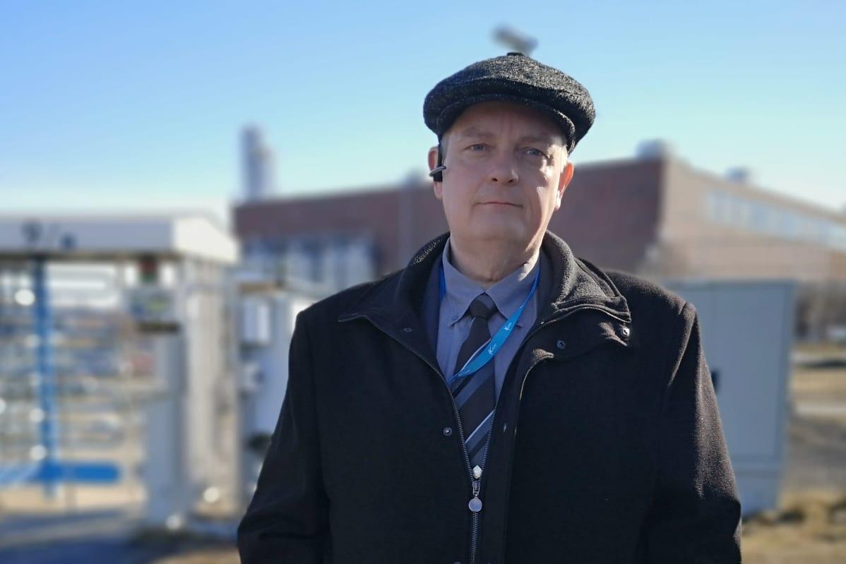 Tummiin pukeutunut Kemin kaupunginjohtaja Matti Ruotsalainen seisoo Veitsiluodon tehtaiden aidan luona, taustalla tehtaan rakennuksia.
