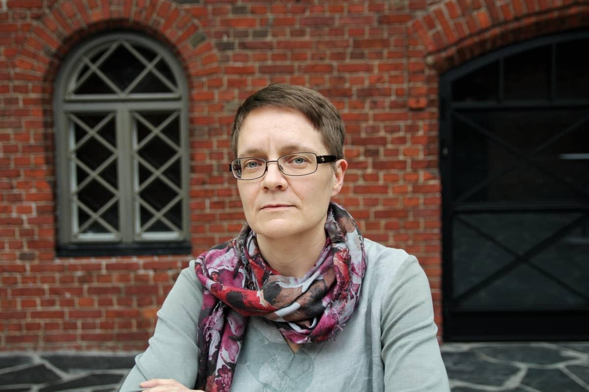Amnesty Internationalin Suomen osaston ihmisoikeuspuolustajien asiantuntija Anu Tuukkanen punatiilisen seinän edessä, vakava ilme kasvoillaan.