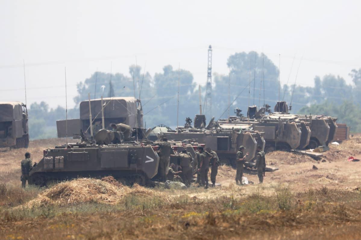 Sotilaita seisomassa ajoneuvojen vieressä.