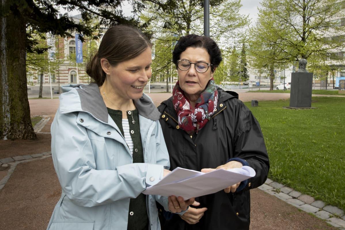 Kirsi Knuuttila ja Aila Paloniemi tutkivat muistiinpanojaan.