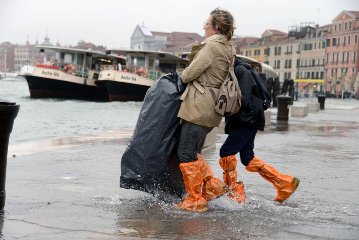 Monet kulkivat Venetsian kaduilla reisin asti ulottuvissa kumisaappaissa.