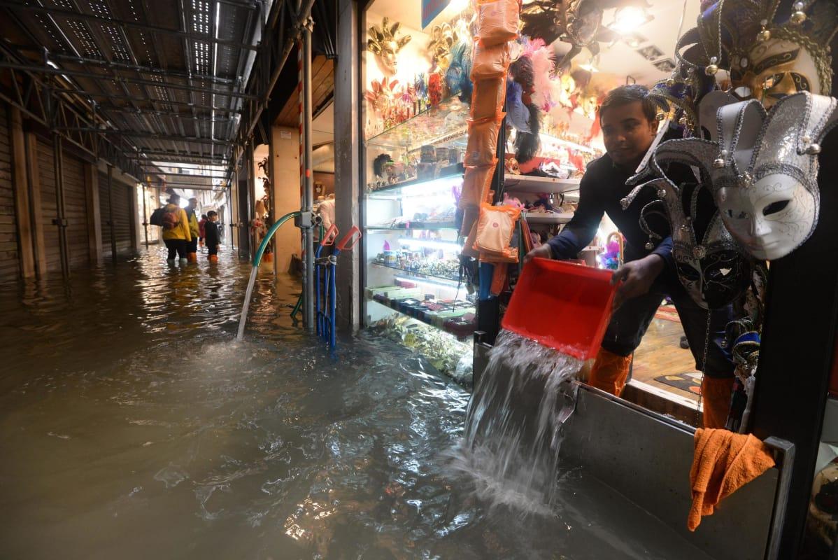 Mies tyhjentää tulvavesien valtaamaa liiketilaansa Venetsiassa 29. lokakuuta 2018.