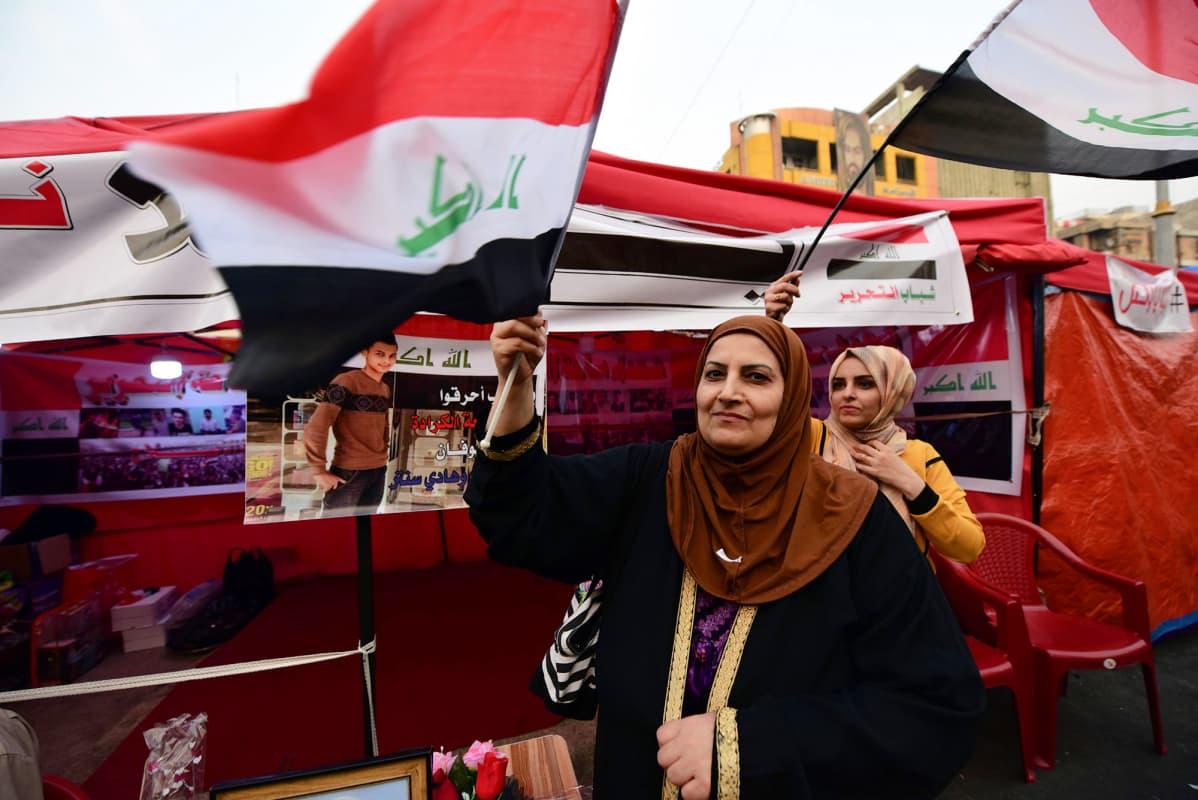 Mielenosoittajat huusivat iskulauseita Bagdadissa Irakin pääministerin Adel Abdul-Mahdin erottua perjantaina.