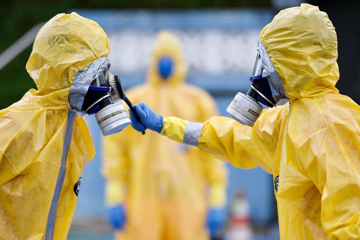 Suojapukuihin pukeutuneet palomiehet puhdistavat suojalasejaan Brasilian Belo Horizontessa.