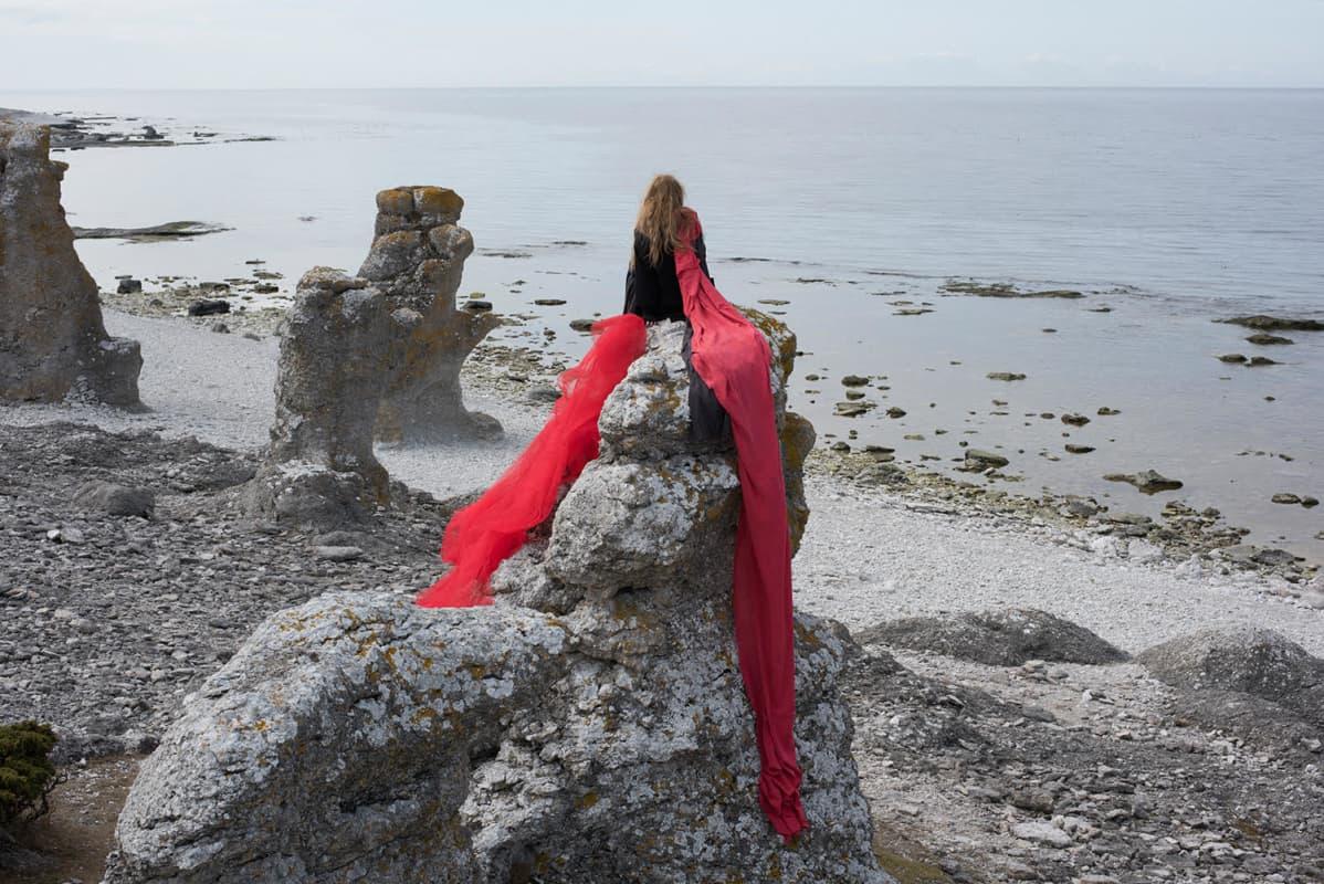 Valokuvateos, jossa nainen istuu kalliolla meren rannalla, katsellen horisonttiin.