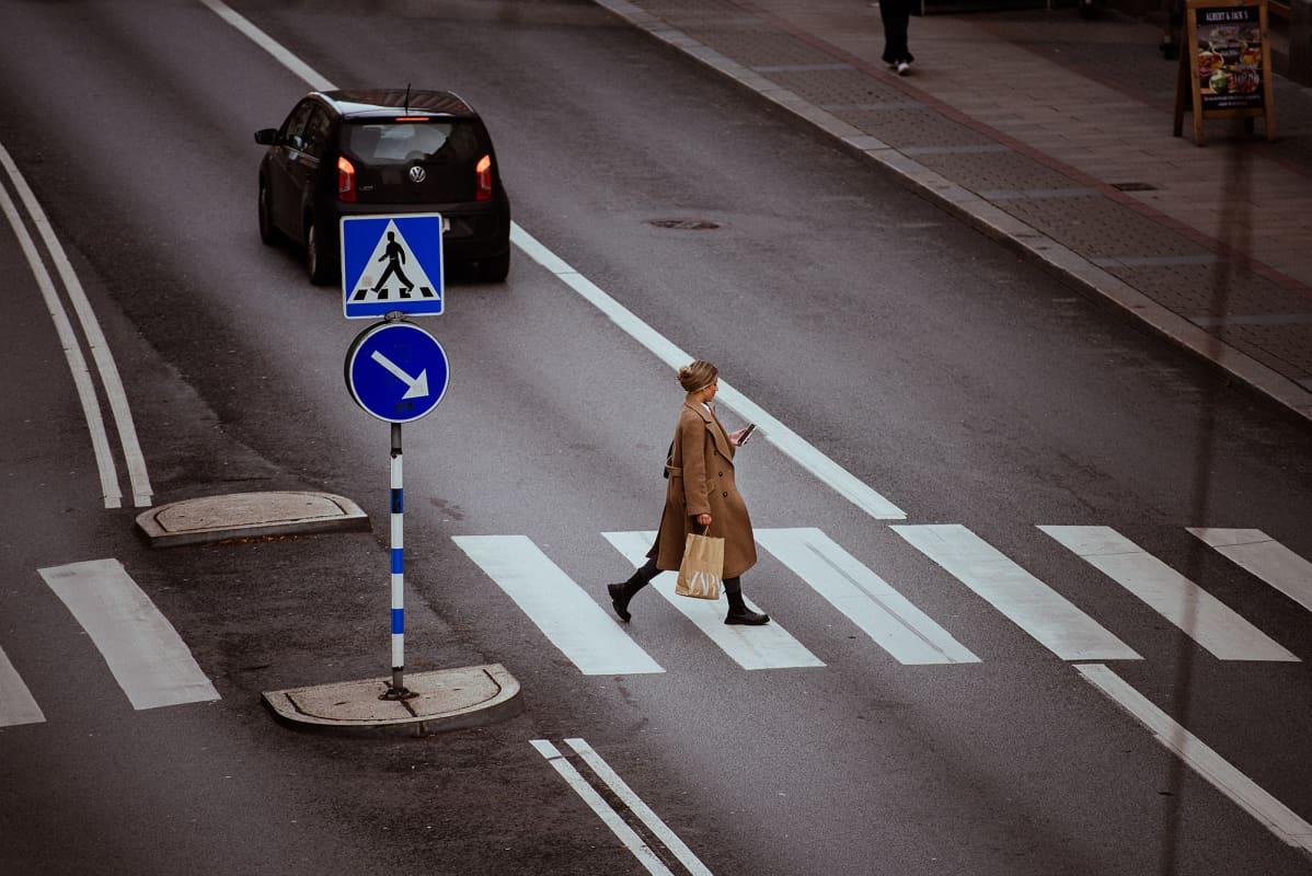 Kuvassa on puhelintaan katsova kävelevä nainen.