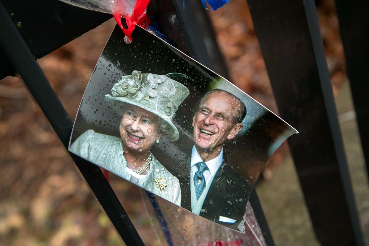 Kuningatar Elisabetia ja prinssi Philipiä esittävä valokuva kiinnitettynä Britannian suurlähetystön aitaan Helsingissä.