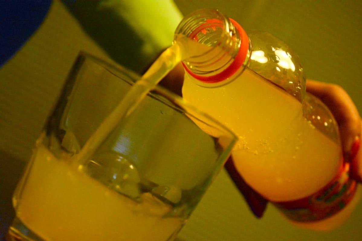 Keltaista limonadia kaadetaan.