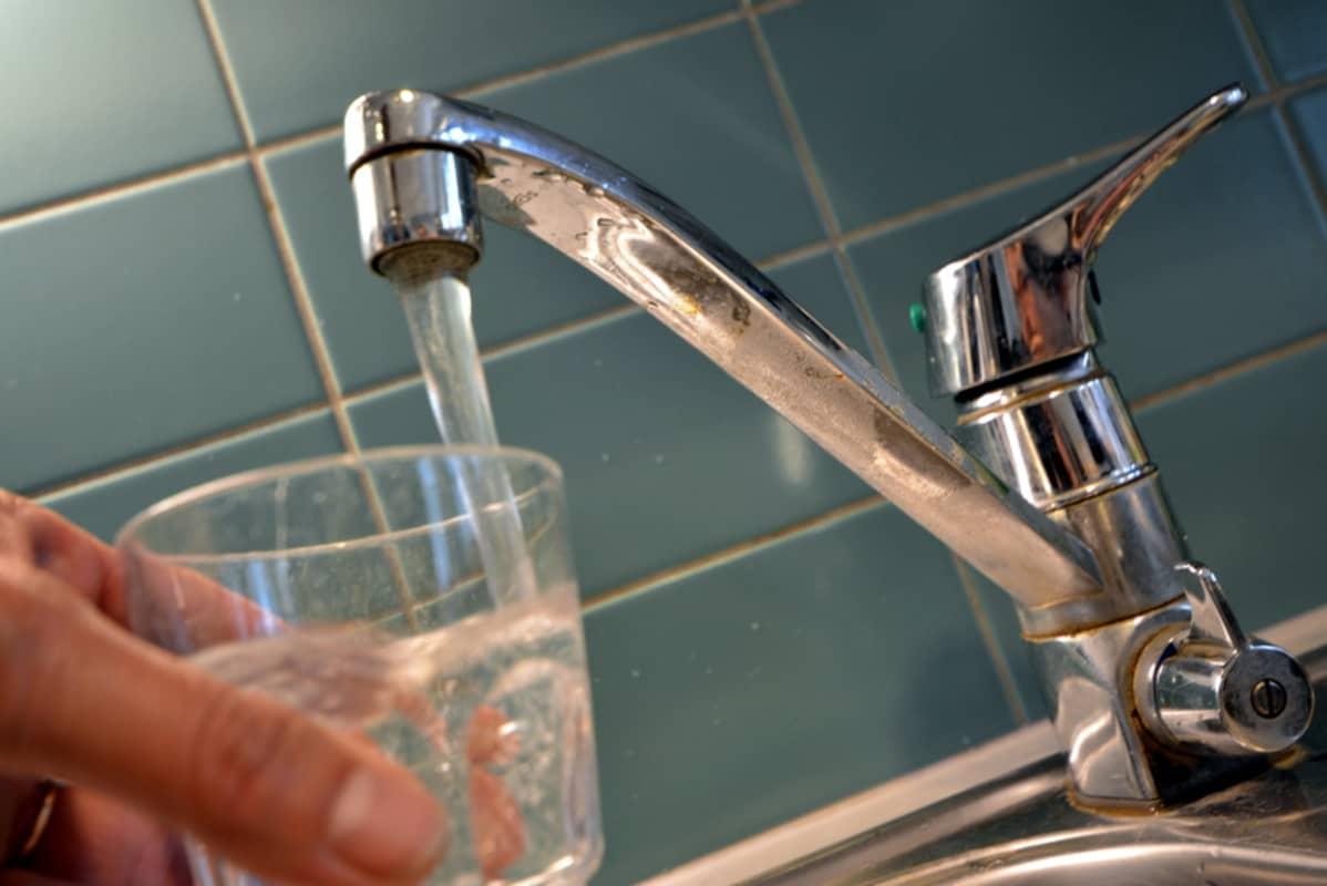 Vettä valutetaan lasiin.