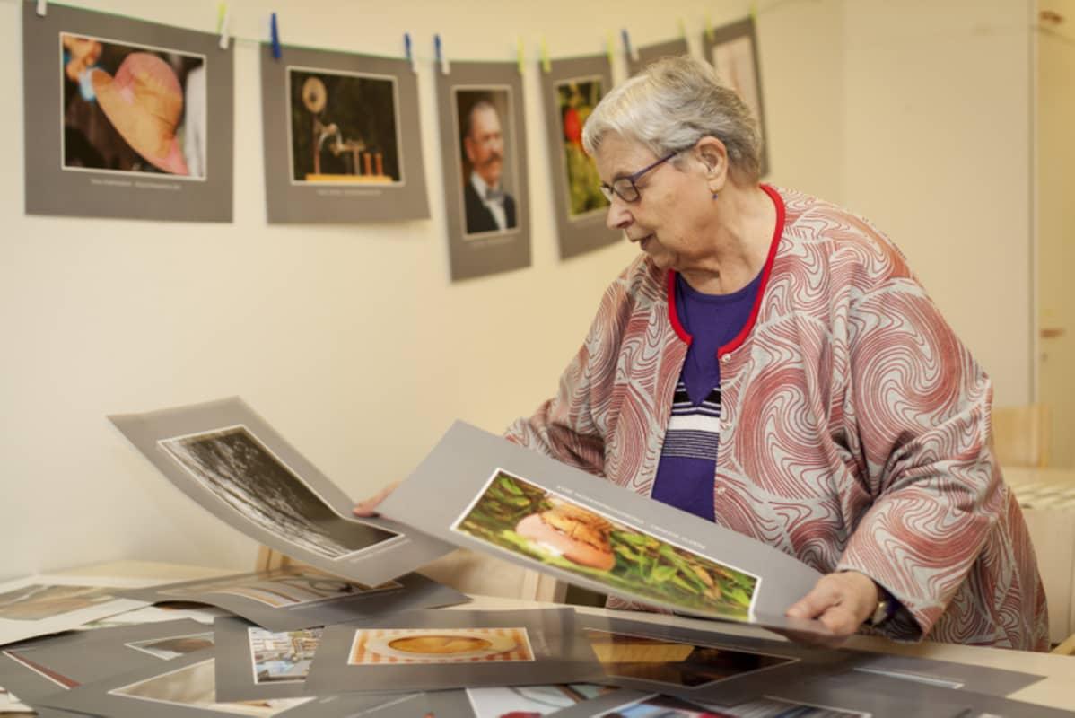 Nainen katselee valokuvia näyttelyssä.