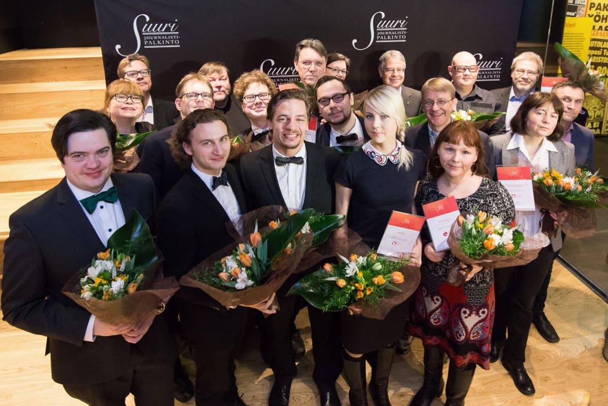 ryhmä ehdokkaita kukkapuskat kädessä