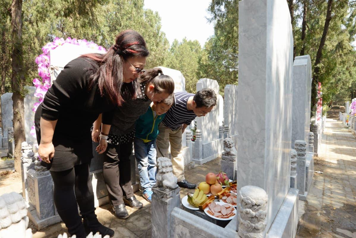 Wangin Yingin perhe kumartaa monta kertaa isovanhempiensa haudalla.