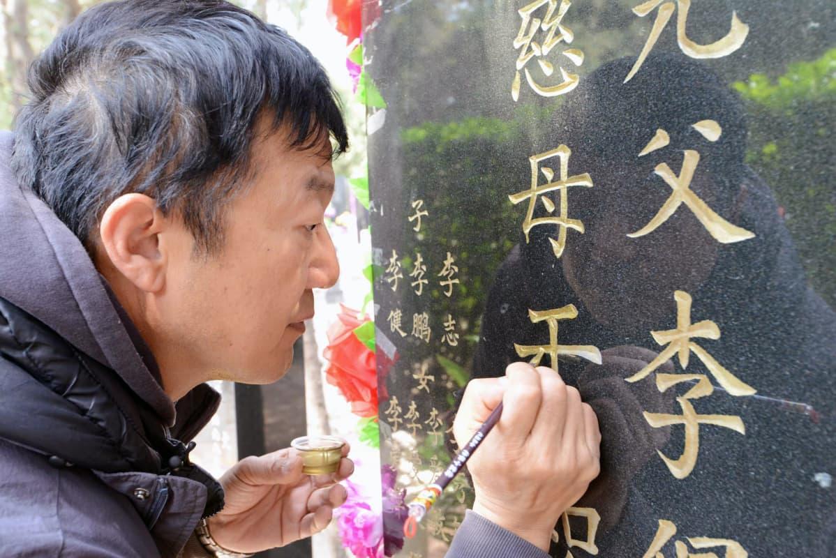 Li Jian maalaa vanhempiensa haudan kultakirjaimet uudelleen.