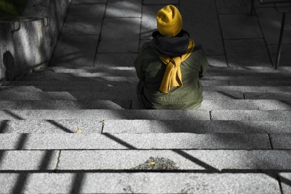 Nainen istuu puiston portailla.