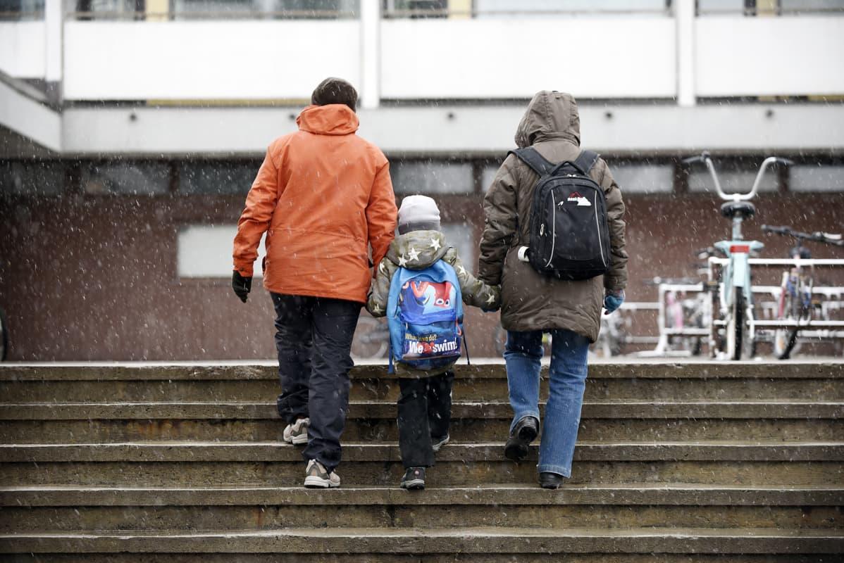 Perhe kävelee ulkoportaissa lumisateessa.