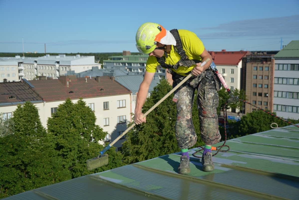 Antti Tervo maalaa kerrostalon kattoa Vaasassa.