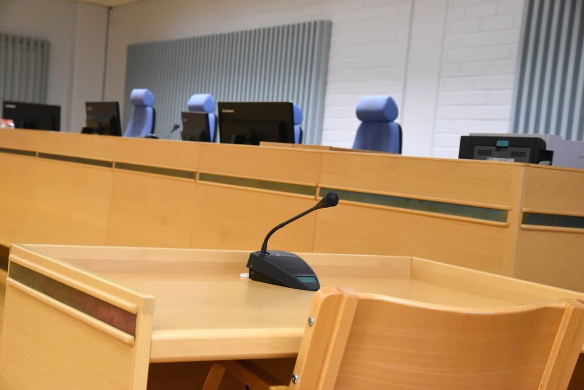 Oulun oikeustalon istuntosali ja todistajan pöytä.