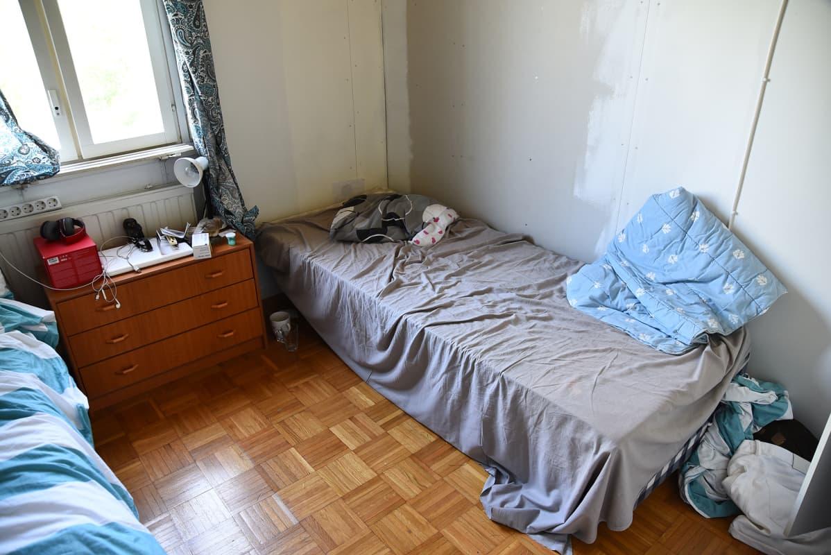 Kaksi petaamatonta sänkyä huoneessa.