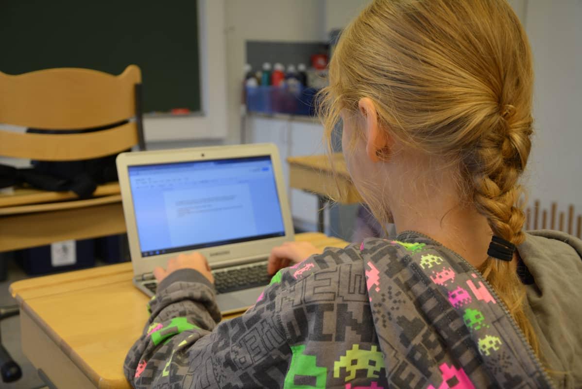 Oppilas käyttää kannettavaa tietokonetta