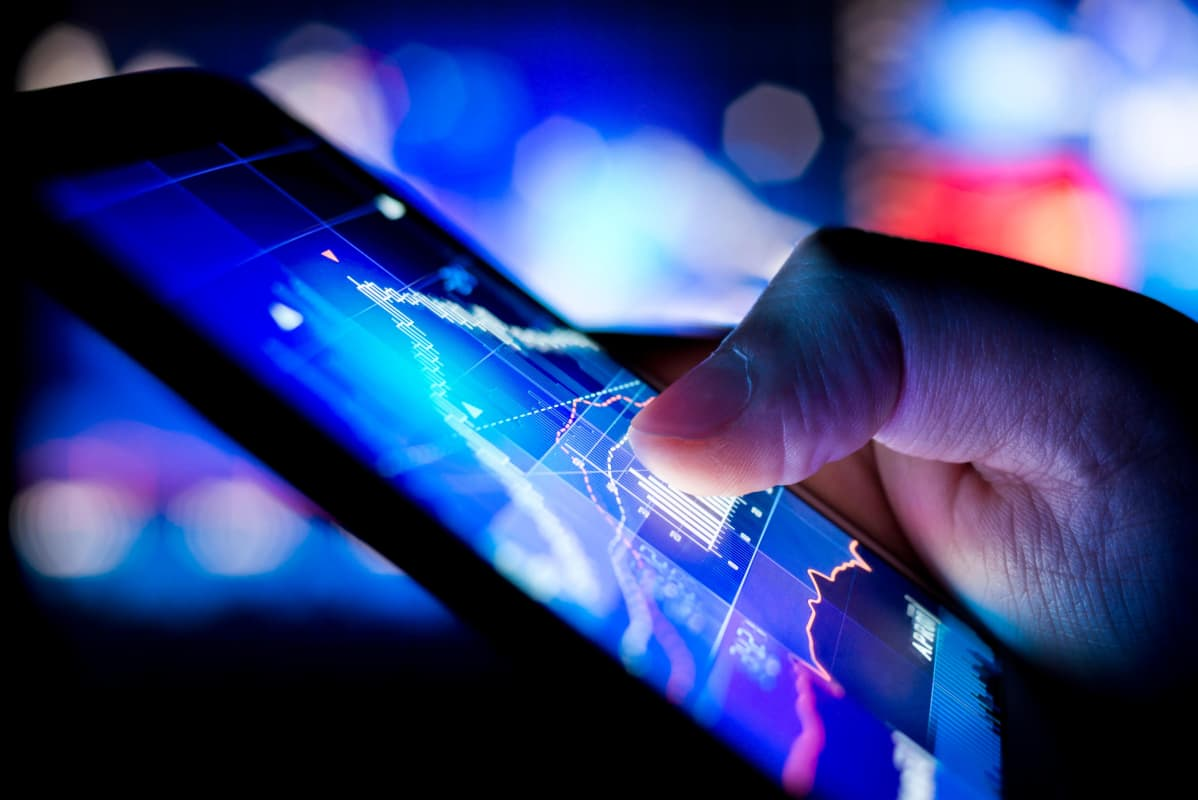 Mies tutkii pörssikurssien kehitystä älypuhelimellaan.