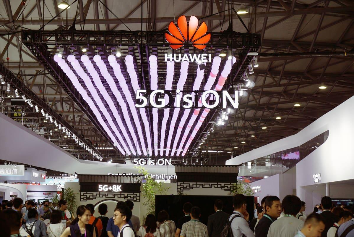 Messuvieraat tutkivat Huawein 5G-puhelimia Shanghaissa.