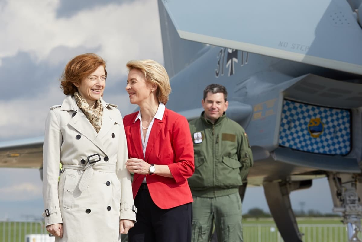 kaksi naista ja mies lentokoneen edessä