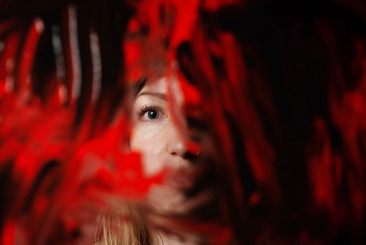 Natalia Kukulas kuvattuna sotketun lasin läpi.
