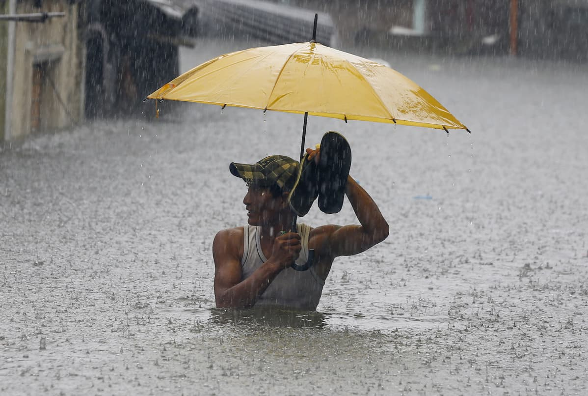 Mies kahlaa tulvavedessä Flippiineillä.