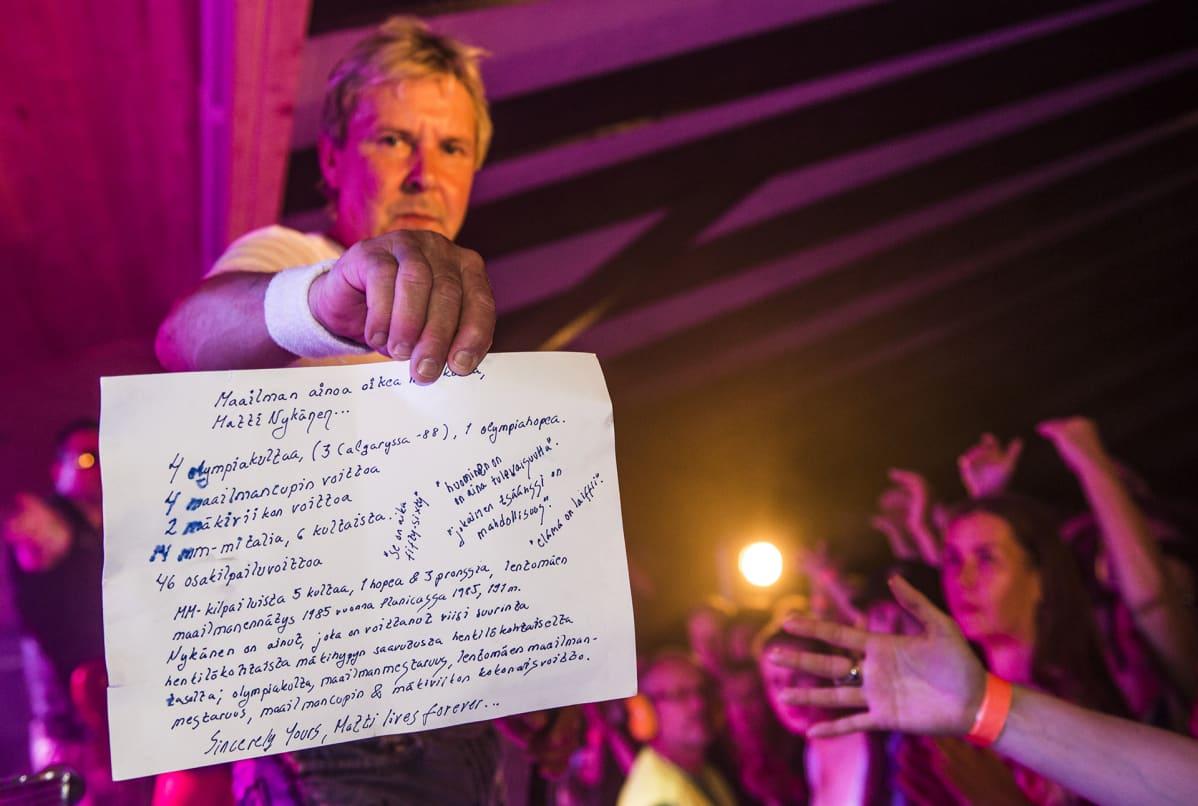 Matti Nykänen näyttää paperia kameralle jossa on lueteltu hänen mitalinsa ja kuolemattomimmat sanonnat.