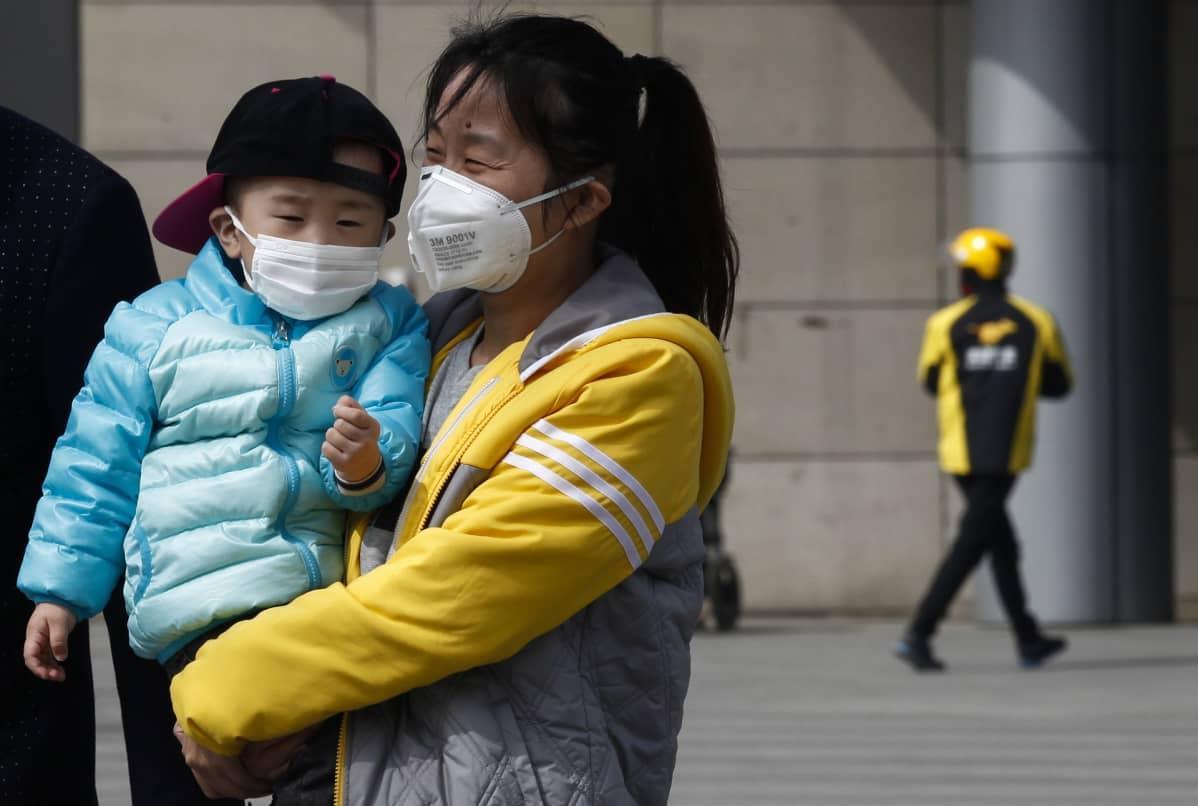 Äiti ja lapsi suojasivat kasvojaan ilmansaasteilta Pekingissä.