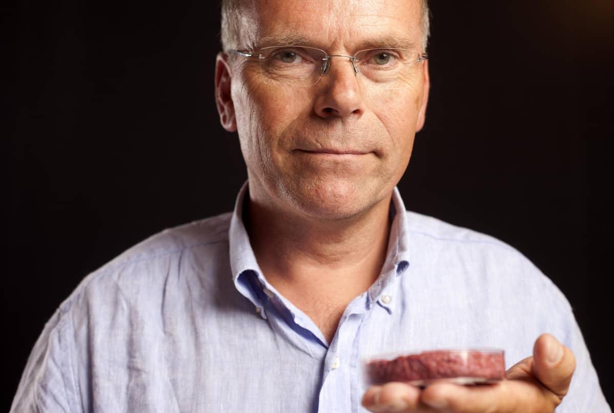 Professori pitää kädessään astiaa, jossa on laboratoriossa kasvatettua lihaa