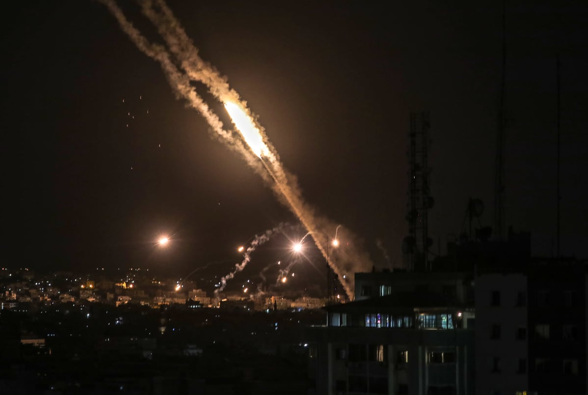 Palestiinalaisten Hamas ampuu raketin kohti Israelia ja raketti valaisee Gazan kaupungin yötaivaan.