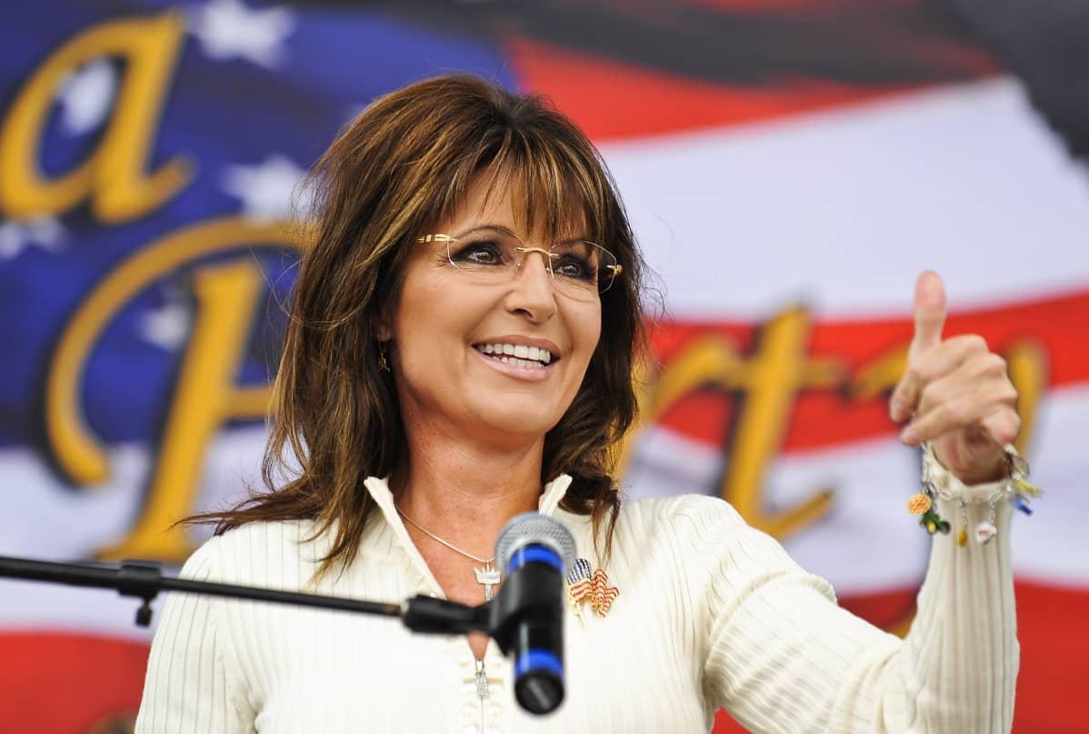 Sarah Palin lähikuvassa näyttää peukkua teekutsuliikkeen tilaisuudessa.