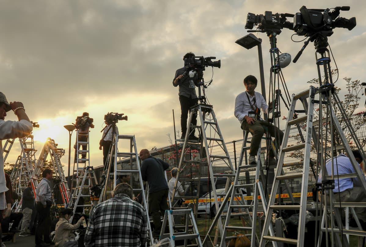 Median kuvaajat seisovat korkeilla A-tikkailla videokameroidensa kanssa.