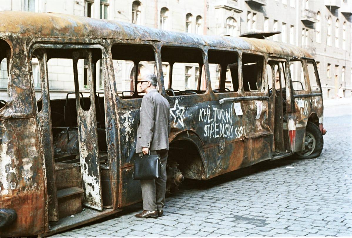 Prahalaismies tarkastelee neuvostovastaisilla iskulauseilla maalattua  palaneen bussin hylkyä.