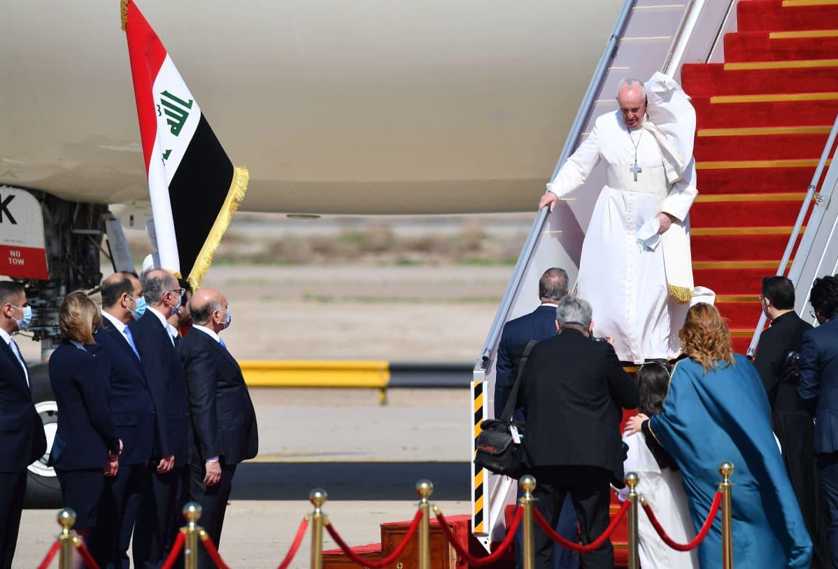Paavi kävelee lentokoneen portaita alas, kaapu lepattaa.