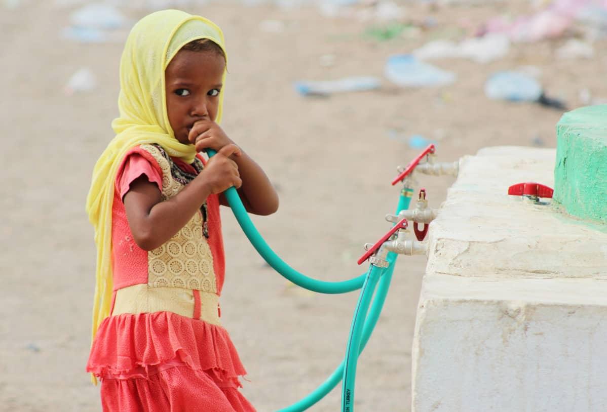 Lapsi juo vettä letkusta.