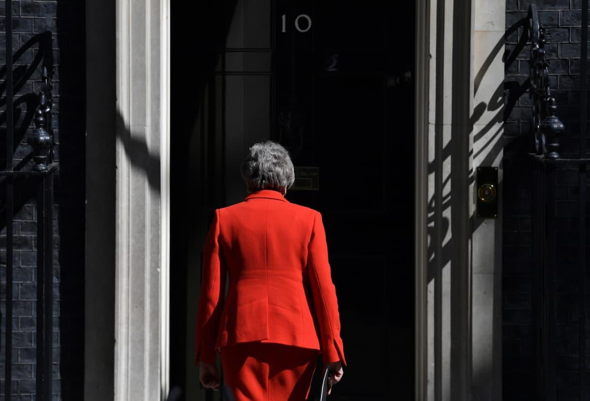 Theresa May kävelee kohti ovea selkä kameraan päin.