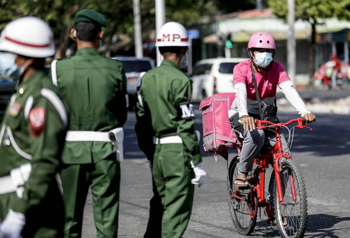 Ruokalähetti ajaa polkupyörällä sotilaspoliisien vieressä Yangonissa.