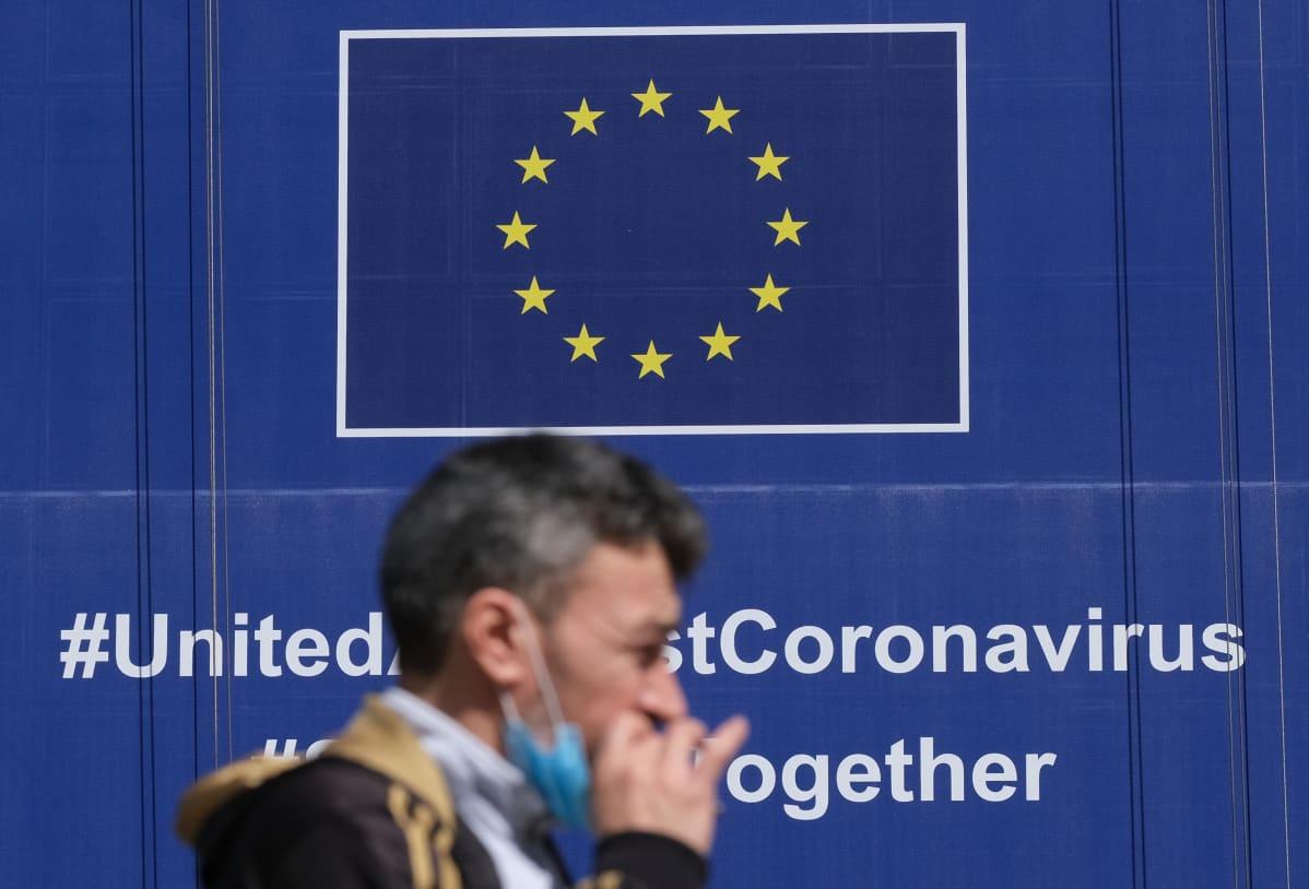 Mies kävelee EU-julisteen ohi, jossa kerrotaan yhteistyöstä koronakriisissä.