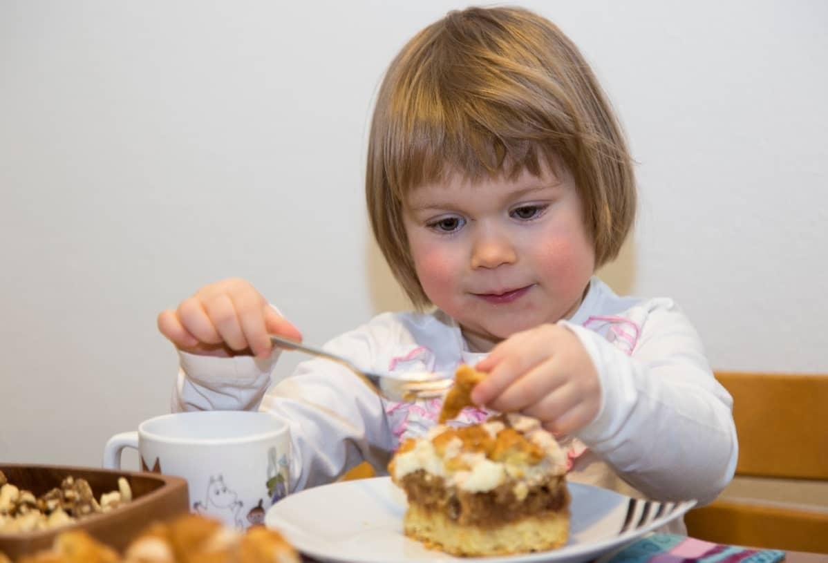 Pieni tyttö syö kakkua haarukalla.