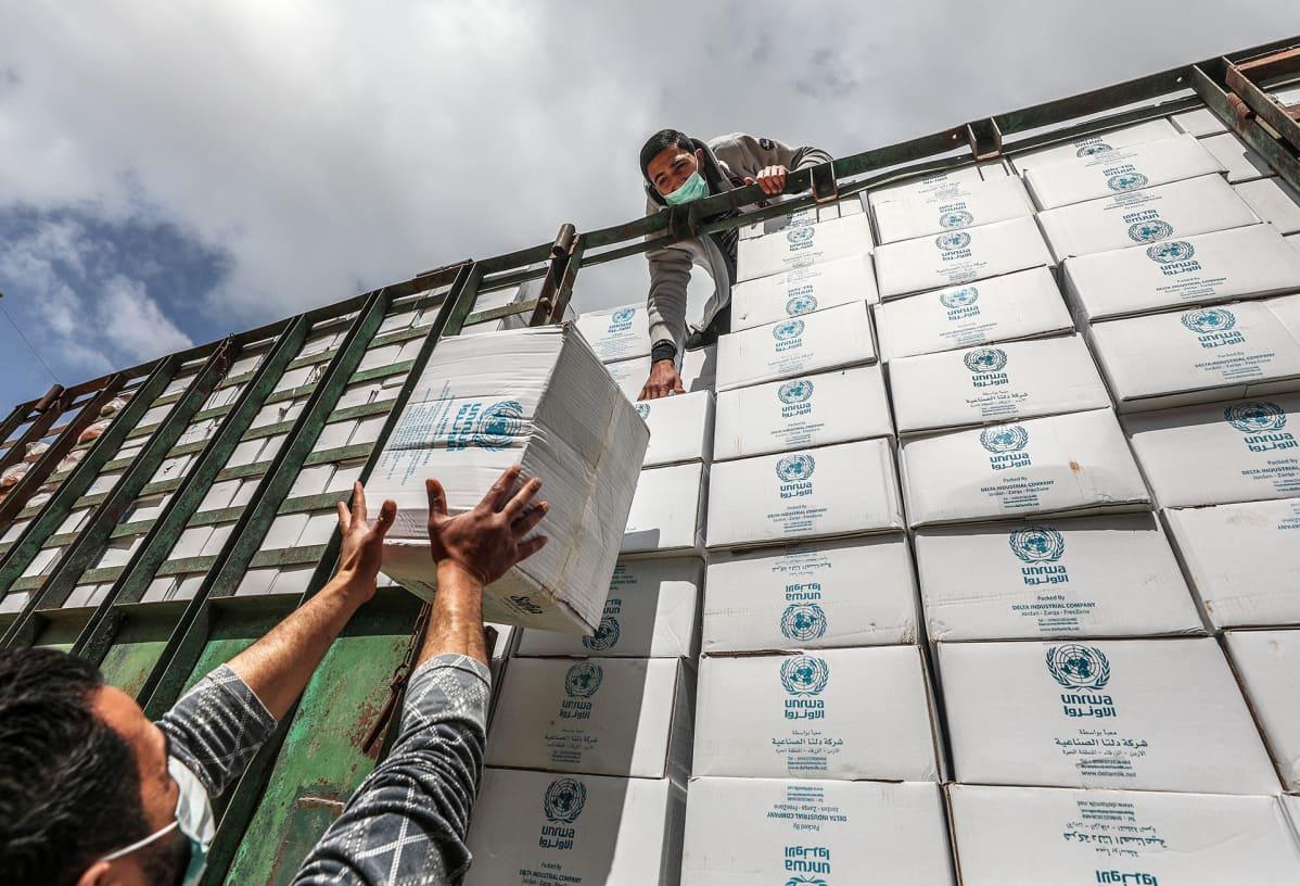UNRWA:n työntekijät lastaavat avustustarvikkeita kuorma-autoon Gazan kaupungissa huhtikuussa 2020.