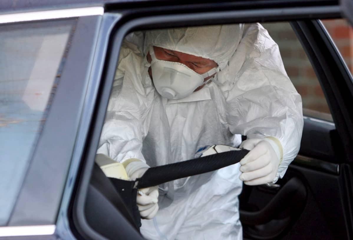 Suojavaattein varustautunut tutkijat tutkii autoa. Murhatutkijat löysivät poloniumia autosta Pohjois-Saksassa sijaitsevassa Haselaussa, missä Dmitri Kovtun oli vieraillut. Kuva joulukuultaa 2006.