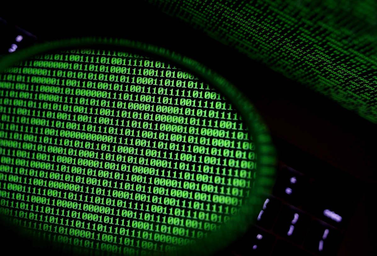 Tietokoneen ruudulla näkyvä binaarikoodi heijastuu peiilistä.