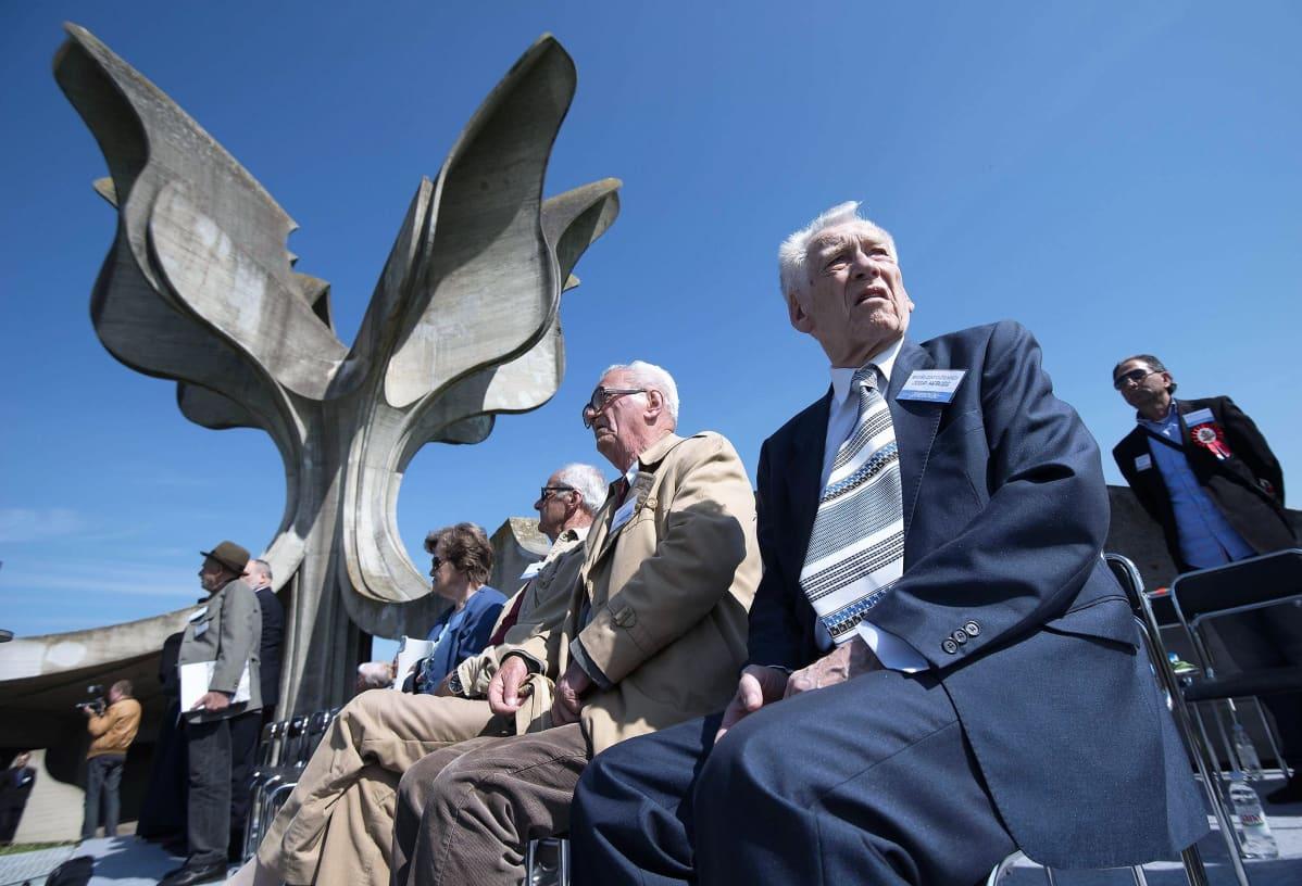 Joukko vanhuksia istuu tuoleilla etualalla. Taustalla näkyy Jasenovacin keskitysleirin paikalle rakennettu muistomerkki, joka on muoodoltaan kuin betonista tehty kukka.