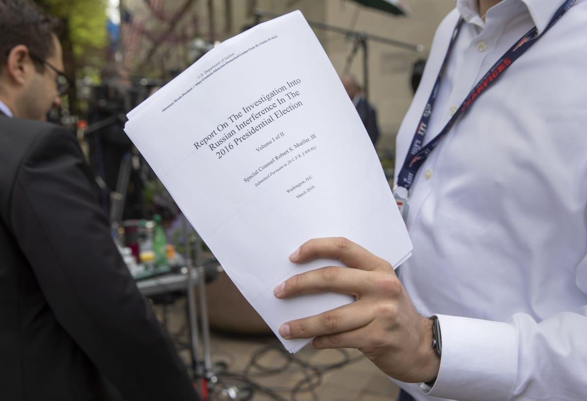 Siinä se nyt on. Toimittaja pitelee printattua, osin salattua Muellerin raporttia.